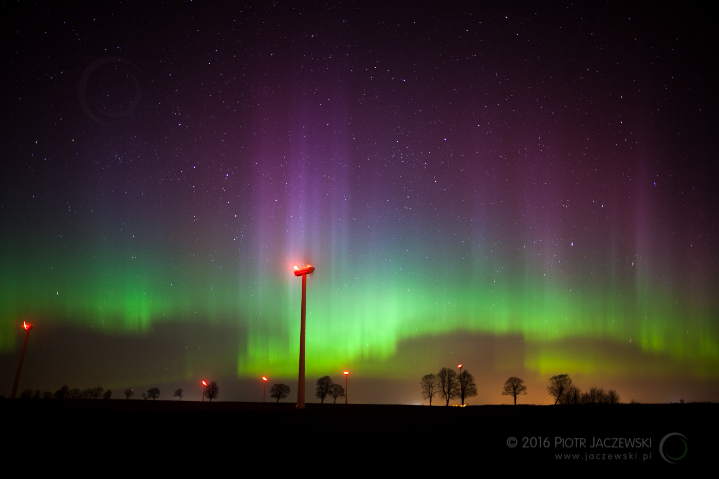 A wind turbine at night with strong Aurora on the sky
